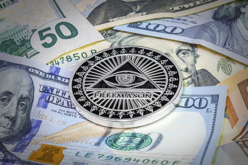 Freemason symbol coin on hundred dollar bills. Cryptocurrency royalty free stock photography