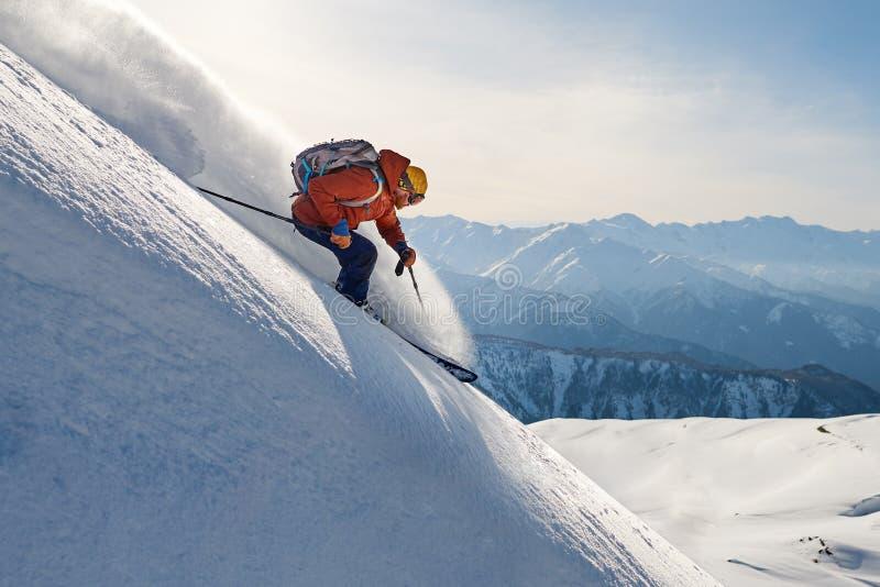 Freeride γύρων σκιέρ στο χιόνι σκονών κάτω από την κλίση ενάντια στο backd στοκ εικόνες με δικαίωμα ελεύθερης χρήσης