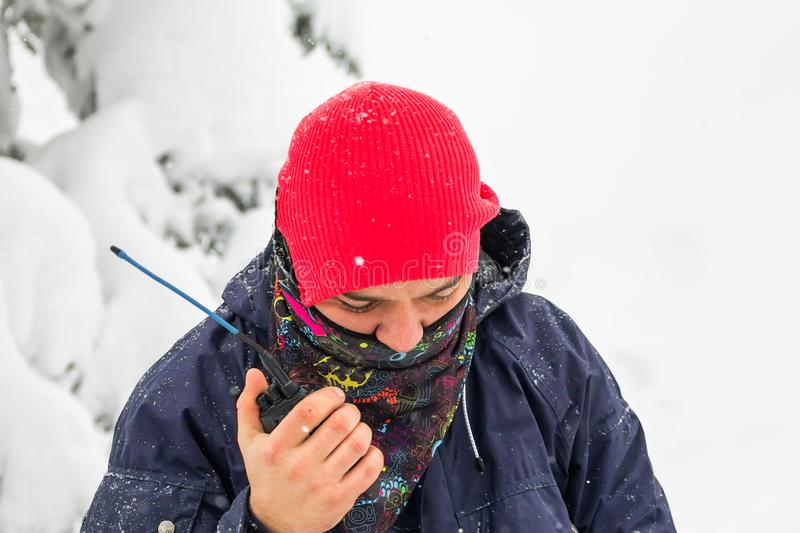 Freerider man talking on a portable radio set in a snowy forest.  royalty free stock photography