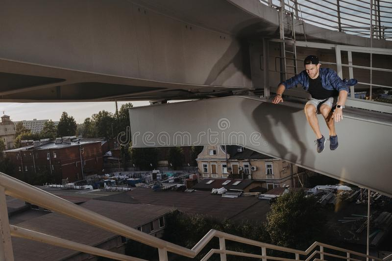Freerun athlete doing scary jump from high bridge. Dangerous parkour royalty free stock photo