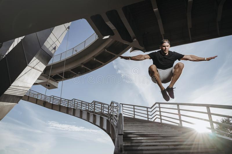Freerunning athlete doing beautiful jump from bridge. Feelling freedom in parkour. Free space for your advertise stock photo
