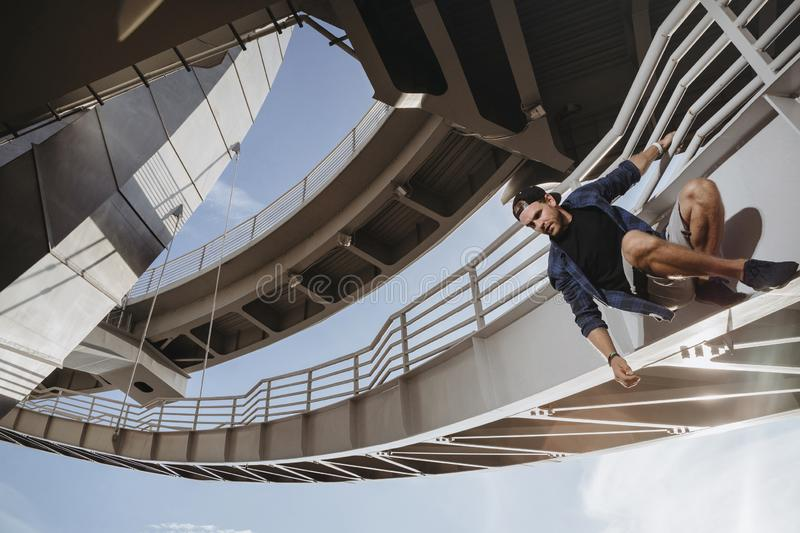 Freerunning athlete is hanging on the bridge and getting ready for a dangerous jump. Parkour in the city stock photography