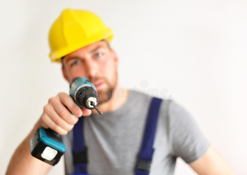 freestanding craftsman construction worker assembler with drilling machine - friendly worker in work clothes on white background royalty free stock photos