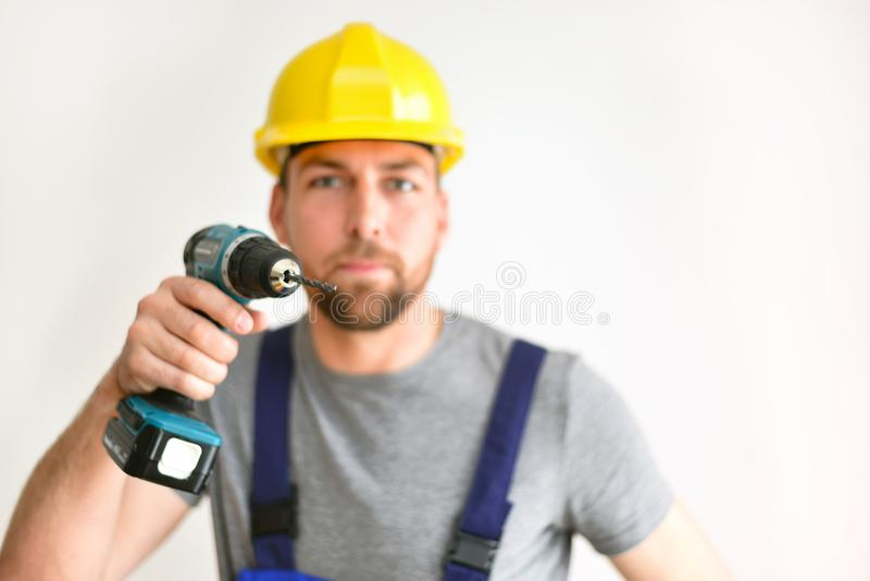 freestanding craftsman construction worker assembler with drilling machine - friendly worker in work clothes on white background stock photography