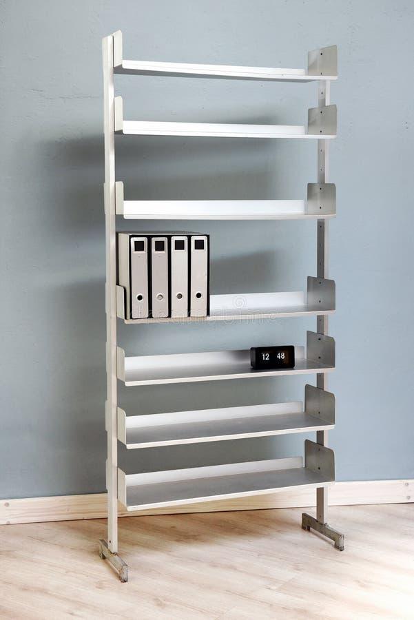 Freestanding metal book shelves. Folders and files on freestanding metal book shelves in modern room stock photos