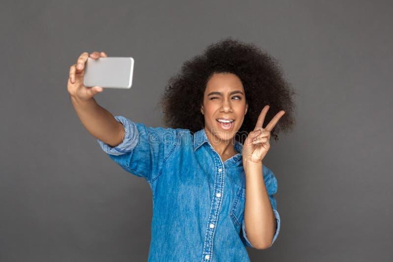 freestyle Η στάση γυναικών μιγάδων που απομονώνεται το κλείσιμο του ματιού στο γκρι που παίρνει selfie στο smartphone που παρουσι στοκ φωτογραφία με δικαίωμα ελεύθερης χρήσης