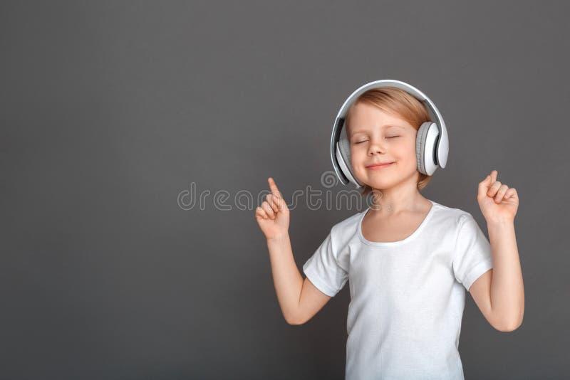 freestyle Μικρό κορίτσι στα ακουστικά που απομονώνεται στην γκρίζα διεύθυνση ματιών ακούσματος κλειστή τραγούδι ευχάριστη στοκ εικόνα με δικαίωμα ελεύθερης χρήσης