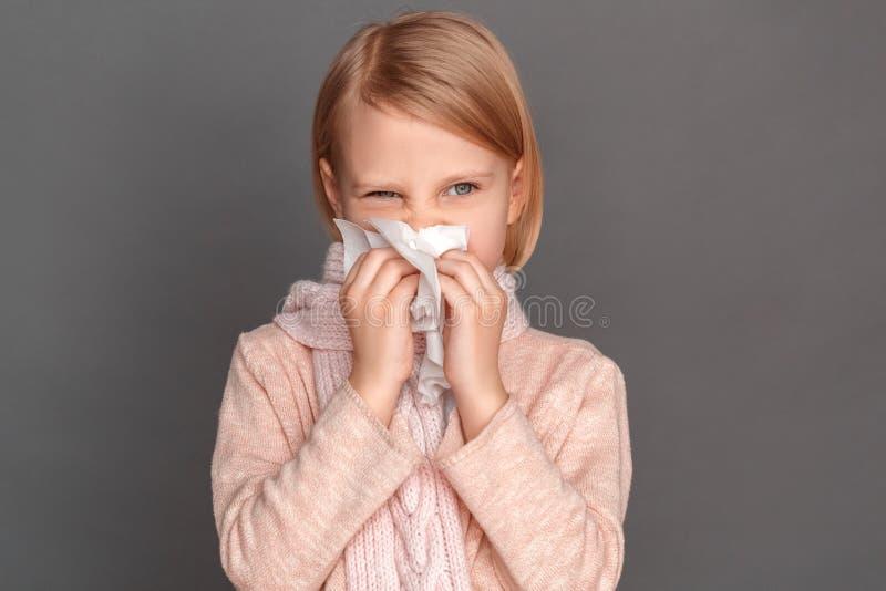 freestyle Μικρό κορίτσι στο μαντίλι που απομονώνεται στην γκρίζα φυσώντας μύτη στον ιστό που φαίνεται κατά μέρος ενδιαφερόμενη κι στοκ φωτογραφίες