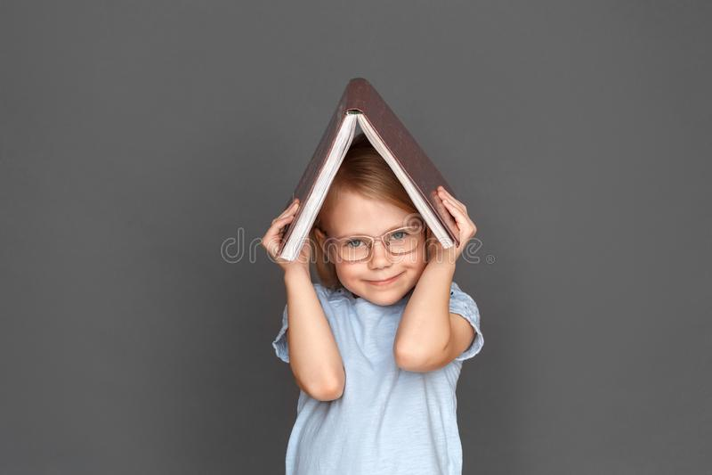 freestyle Μικρό κορίτσι eyeglasses στο γκρίζο κρύψιμο κάτω από το χαμόγελο βιβλίων χαριτωμένο στοκ εικόνες με δικαίωμα ελεύθερης χρήσης