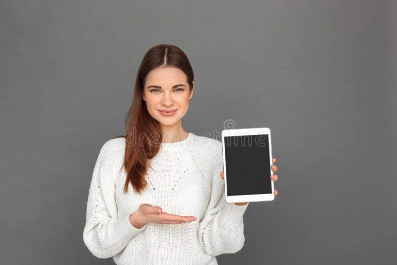 freestyle Νέο κορίτσι που στέκεται στο γκρι που παρουσιάζει οθόνη του ψηφιακού χαμόγελου ταμπλετών φιλικού στοκ φωτογραφίες