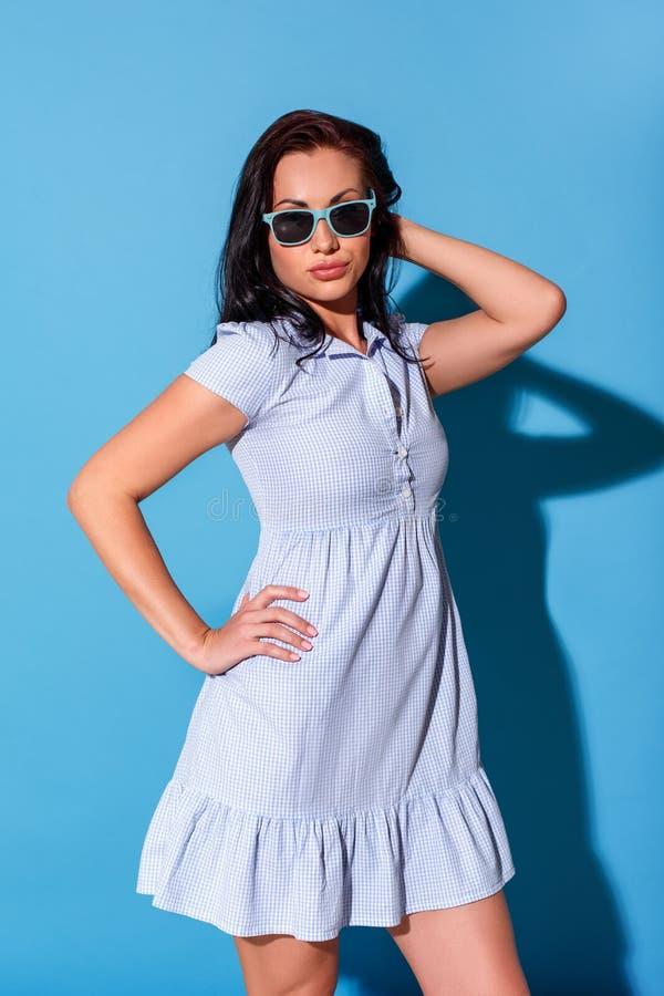 freestyle De vrouw in kleding en zonnebril de status geïsoleerd op blauwe muur overhandigen op heupen wat betreft haar kijkend ca royalty-vrije stock afbeelding