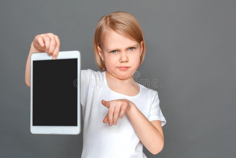 freestyle Het meisje op grijs wordt geïsoleerd die het scherm van digitaal tabletclose-up tonen die aan camera richten die niet b stock foto's