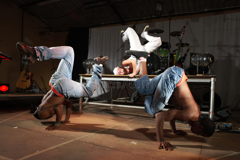 Freestyle hip-hop dancers. Three Freestyle hip-hop dancers in a dancing practice session on stage with instruments. Lit with spotlights. Movement on edges of royalty free stock photo
