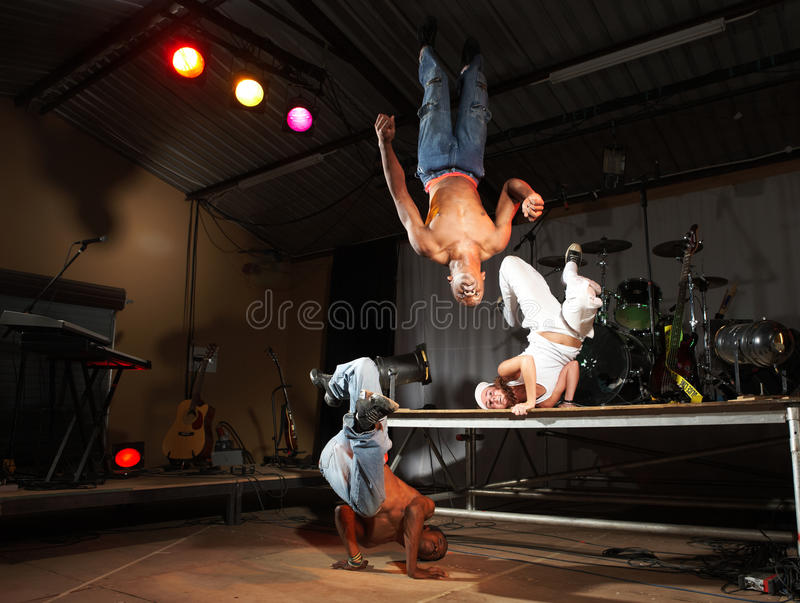 Freestyle hip-hop dancers. Three freestyle hip-hop dancers in a dancing practice session on stage with instruments. Lit with spotlights. Movement on edges of stock photography
