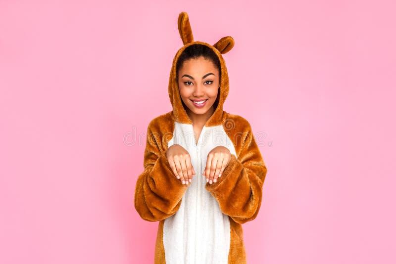 freestyle Jonge vrouw die in kigurumi op roze posint ot camera wordt zich geïsoleerd bevinden die als konijn gelukkig glimlachen royalty-vrije stock foto