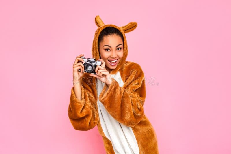freestyle Jonge vrouw die in kigurumi op roze wordt zich geïsoleerd bevinden die die foto's met camera speels glimlachen nemen royalty-vrije stock fotografie