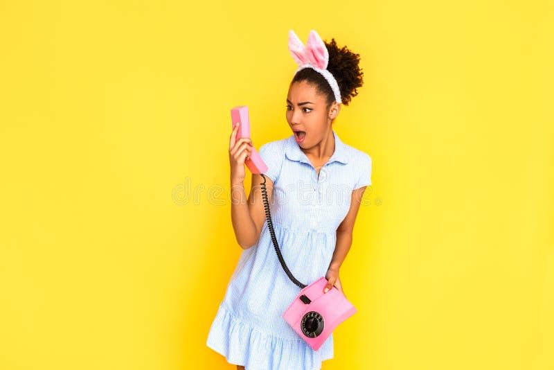 freestyle Jonge vrouw in leuke kleding en konijntjesoren status geïsoleerd op geel met stationaire telefoon die zaktelefoon bekij royalty-vrije stock foto