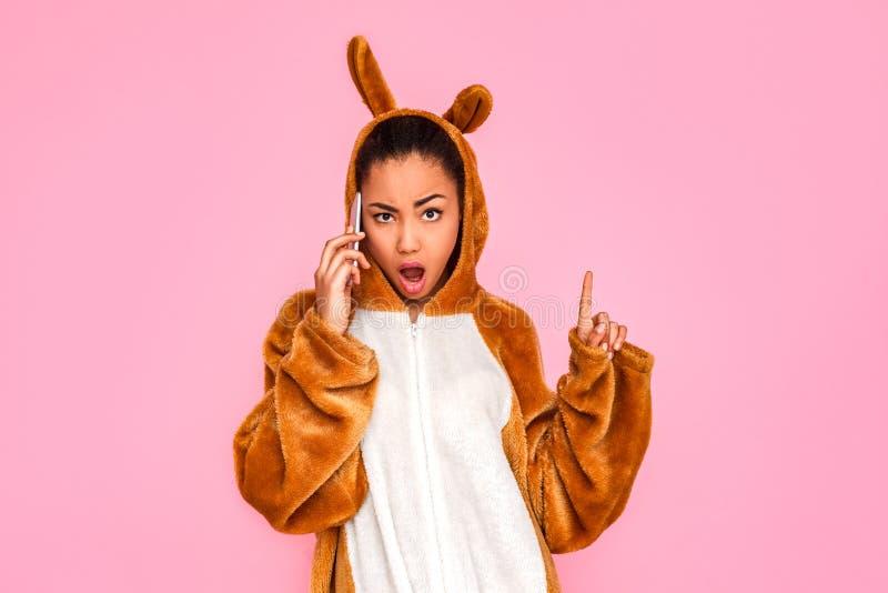 freestyle Jovem mulher na posição do kigurumi na fala cor-de-rosa no telefone que olha a câmera sassy foto de stock