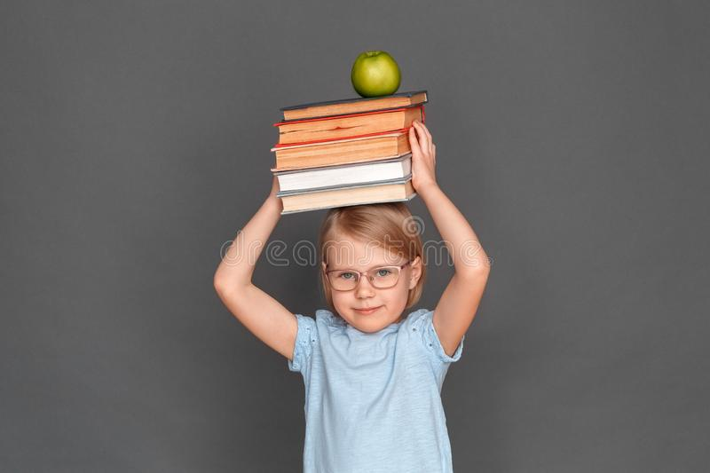 Freestyle. Little girl in eyeglasses isolated on grey with books and apple above the head smiling joyful royalty free stock images