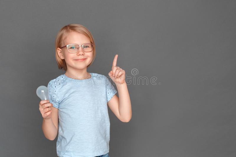 Freestyle. Little girl in eyeglasses isolated on grey with light bulb pointing up smiling confident royalty free stock image