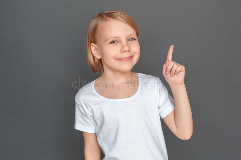 Freestyle. Little girl isolated on grey pointing at space aside smiling joyful close-up stock photography