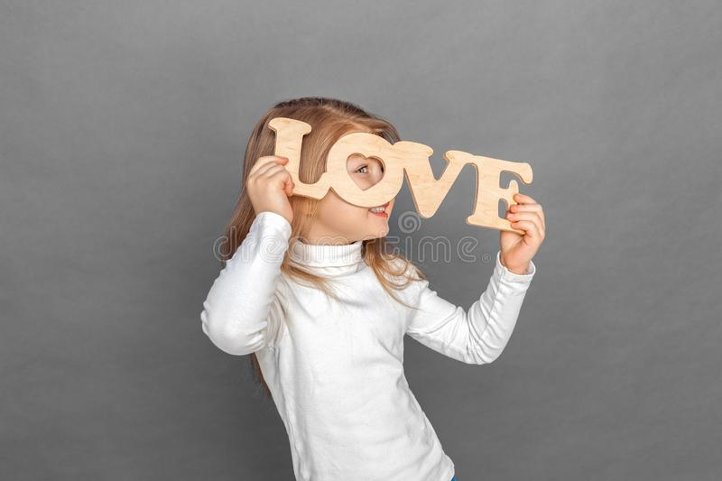 Freestyle. Little girl standing isolated on grey looking through love sign smiling playful royalty free stock photo