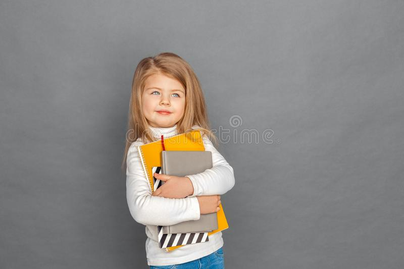 Freestyle. Little girl standing isolated on grey with notebooks looking aside smiling dreamful stock photo
