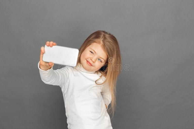 Freestyle. Little girl standing isolated on grey taking selfie on smartphone smiling playful stock photography