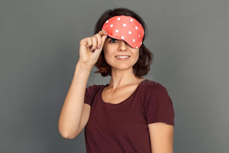freestyle Młoda kobieta w dosypianie masce odizolowywającej na popielatej przyglądającej kamerze rozochoconej obrazy royalty free