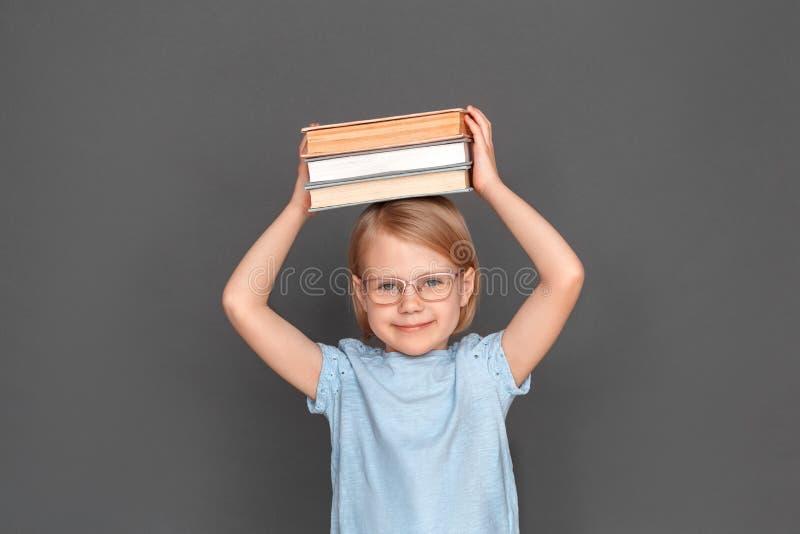 freestyle Mała dziewczynka w eyeglasses odizolowywających na popielatym z książkami nad kierowniczy uśmiechnięty rodzaj obraz royalty free