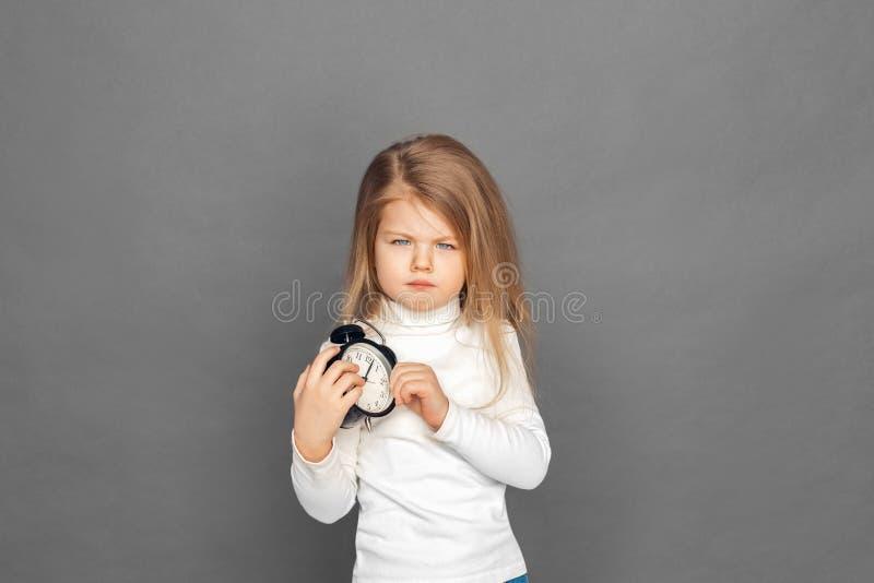 freestyle Meisje die op grijs met wekker grimassen trekken wordt zich geïsoleerd bevinden die ongelukkig aan camera royalty-vrije stock afbeeldingen