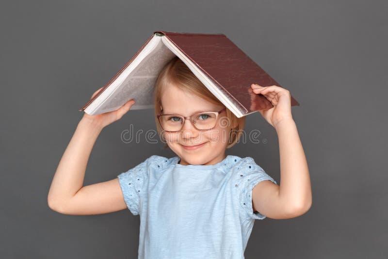 freestyle Meisje in oogglazen op grijs wordt geïsoleerd die hoofd behandelen met boek die speels close-up glimlachen dat royalty-vrije stock foto's