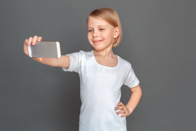 freestyle Meisje op grijs wordt geïsoleerd die selfie bij smartphone het stellen aan gelukkige die camera nemen stock afbeelding