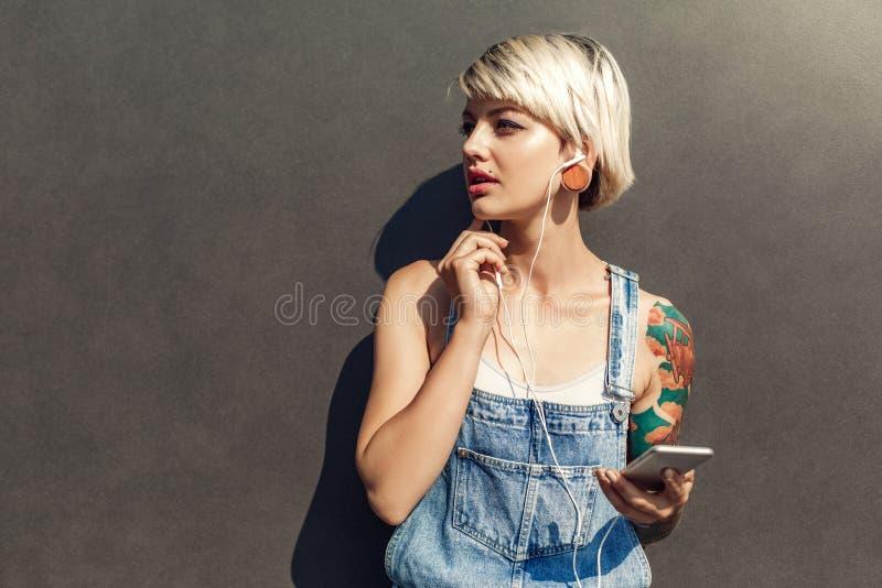 freestyle Muchacha alternativa en los auriculares que se colocan aislados en gris en la calle de la ciudad con música que escucha fotos de archivo