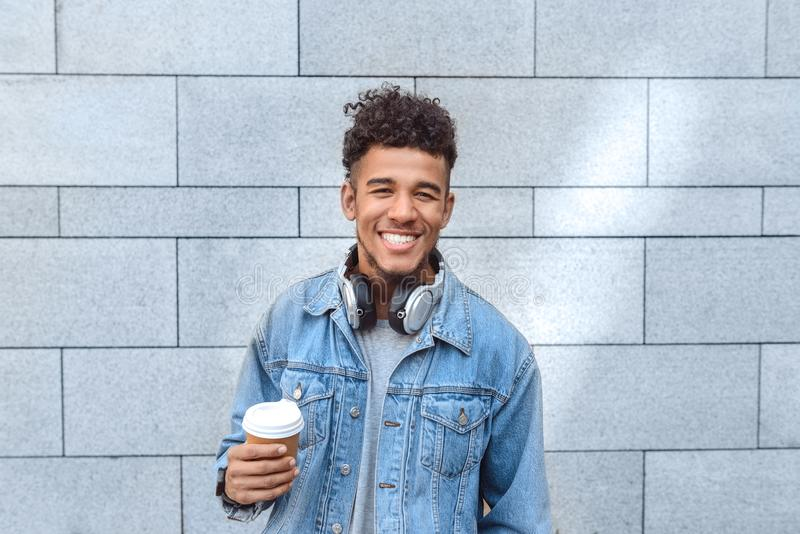 Freestyle. Mulatto guy with headphones on neck standing isolated on wall with cup of coffee smiling toothy royalty free stock photography