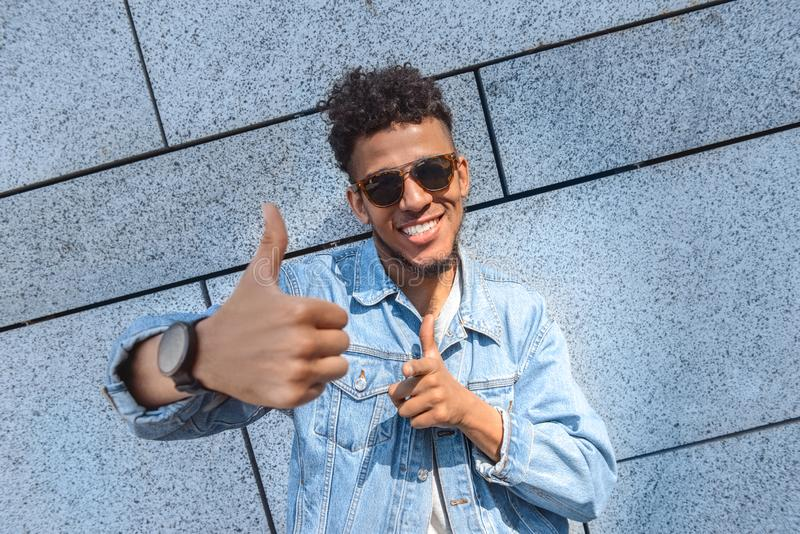 Freestyle. Mulatto guy in sunglasses standing isolated on wall showing thumb up smiling cheerful close-up royalty free stock photos