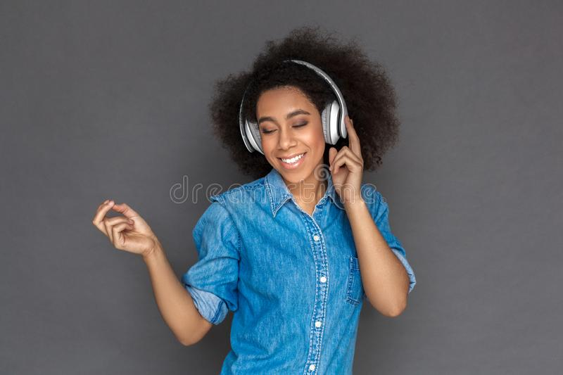 Freestyle. Mulatto woman in headphones standing isolated on grey listening favorite song closed eyes cheerful royalty free stock images