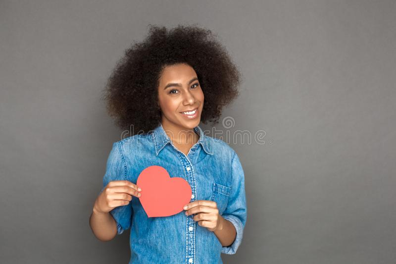 Freestyle. Mulatto woman standing on grey with heart shape card smiling happy royalty free stock photo