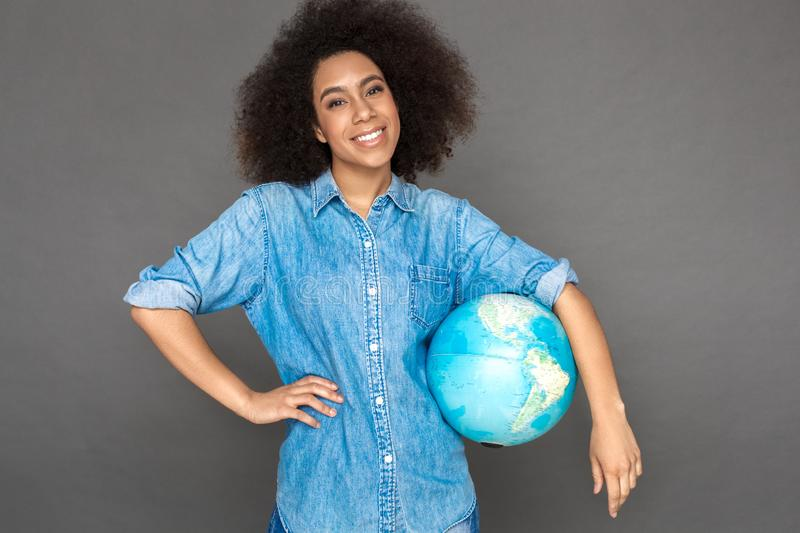 Freestyle. Mulatto woman standing on grey with terrestrial globe smiling happy stock photo
