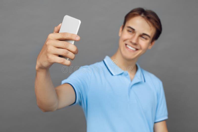 freestyle Nastolatek chłopiec pozycja odizolowywająca na popielatym bierze selfie na smartphone w górę szczęśliwy zamazanego fotografia royalty free