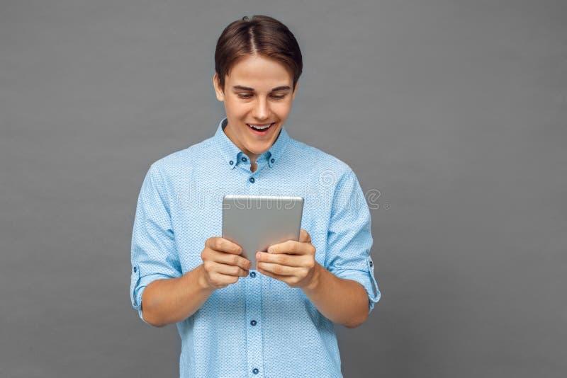 freestyle Nastolatek chłopiec pozycja odizolowywająca na popielatym używa app na cyfrowej pastylce z podnieceniem obraz royalty free
