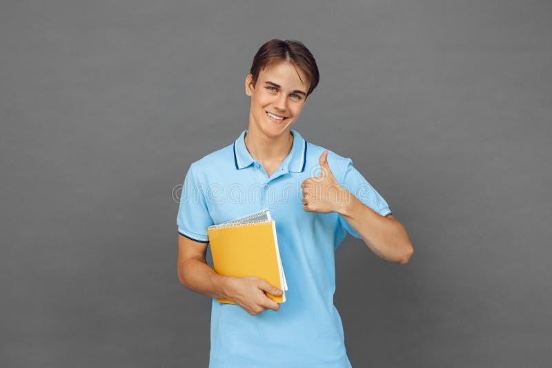 freestyle Nastolatek chłopiec pozycja odizolowywająca na popielatym z notatnika kciukiem w górę ono uśmiecha się figlarnie fotografia stock