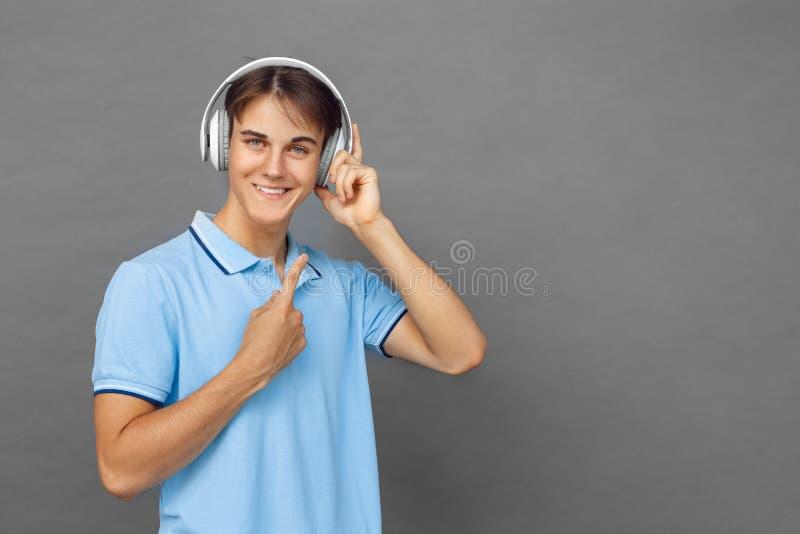 freestyle Nastolatek chłopiec wskazuje w górę headphons stoi przy odizolowywający na popielaty słuchający muzyczny ono uśmiecha s obrazy stock
