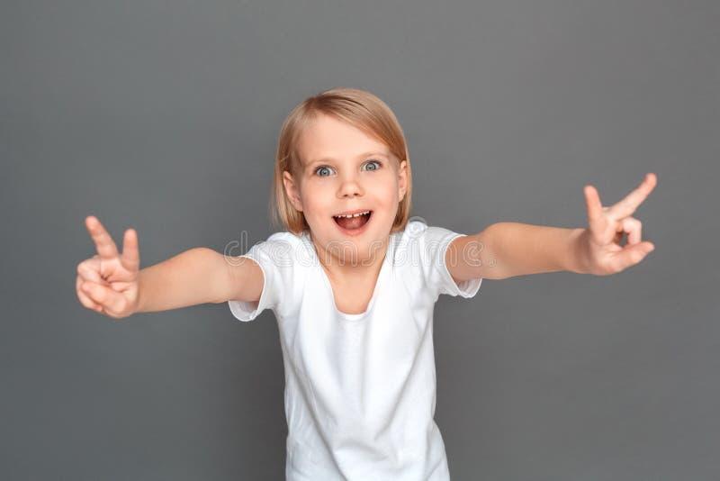freestyle Niña aislada en la sonrisa fresca gris del gesto que muestra emocionada foto de archivo