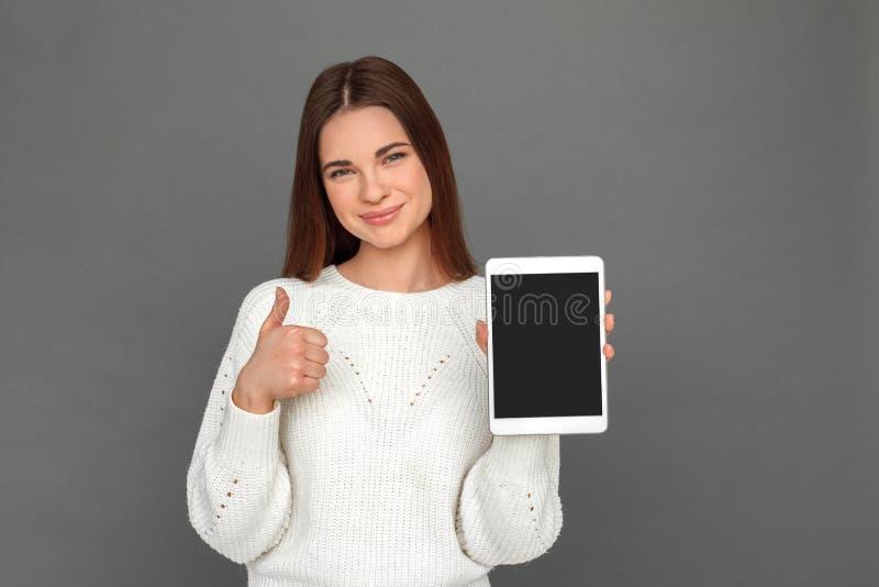 freestyle Posição da moça isolada na tela mostrando cinzenta do polegar digital da tabuleta acima do sorriso feliz imagens de stock royalty free