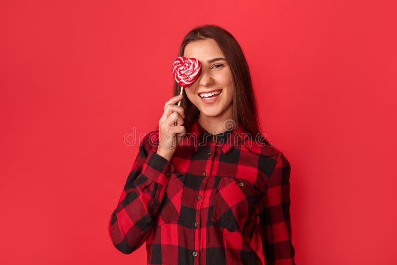 freestyle A posição da moça isolada no olho de coberta vermelho com coração deu forma ao riso do pirulito brincalhão imagem de stock