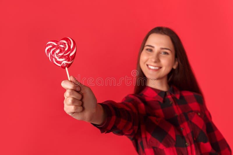 freestyle Posição da moça no vermelho com o feliz de sorriso dado forma coração do close-up do pirulito borrado imagens de stock