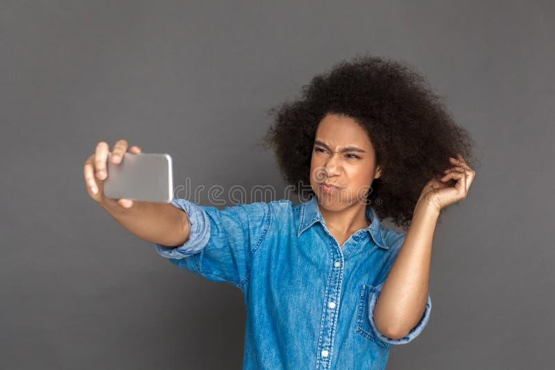freestyle Position de femme de mulâtre d'isolement sur le selfie de prise gris sur les lèvres boudantes de smartphone mécontentes photo libre de droits