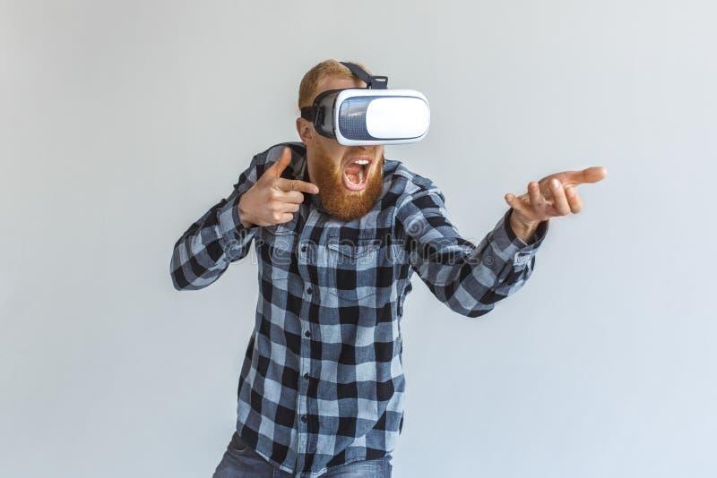 freestyle Rijpe mens in virtuele werkelijkheidshoofdtelefoon status geïsoleerd bij het grijze spelen die met denkbeeldig kanon sc royalty-vrije stock foto's