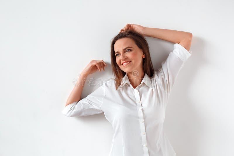 freestyle Situación de la mujer aislada en blanco inclinando detrás la sonrisa relajada foto de archivo